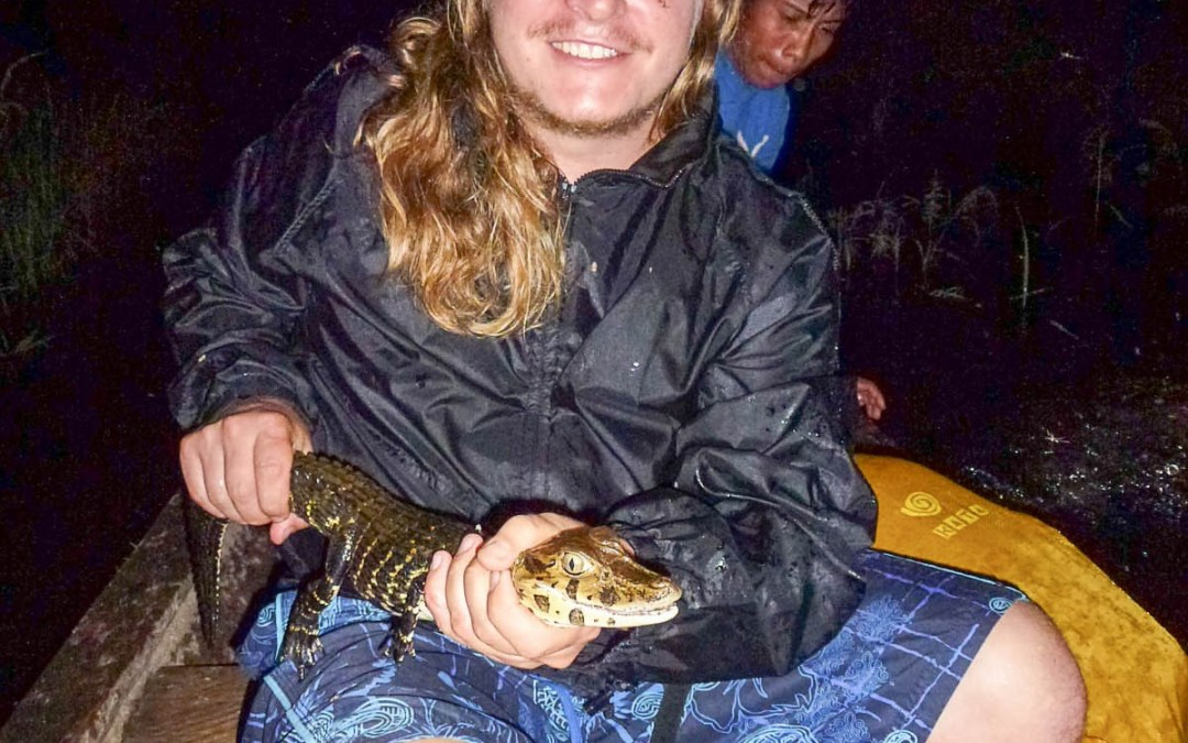 Photo: Nile holding caiman, Amazon jungle near Iquitos, Peru