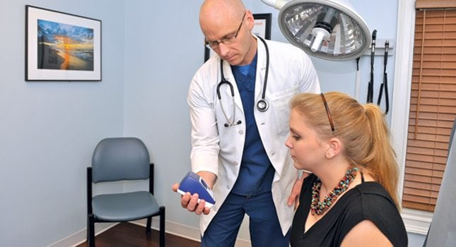 A doctor shows a patient test results on the BD Veritor™ System.