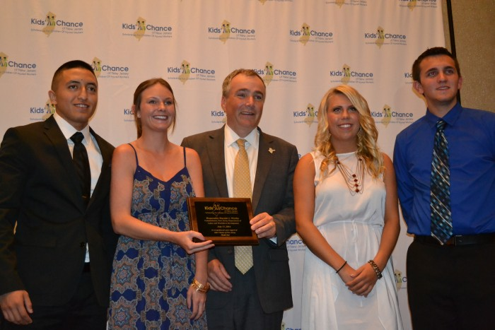 New Jersey Labor Commissioner Harold J. Wirths (center) holds a plaque commemorating his support for Kid's Chance New Jersey, which issued six scholarships, each for $10,000, to students who had a parent killed or catastrophically injured at work. Scholarship recipients included (from left to right) Pedro Morejon, Alexandra Kurnath, Mackenzie Kurnath and Scott Kwiatek. The two other scholarship recipients were Marie Molinaro and Trent Schamble.