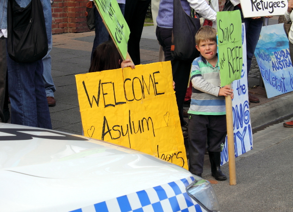 "A young boy urges Tony Abbott to ""save the reef"". Photo: Wayne Jansson"