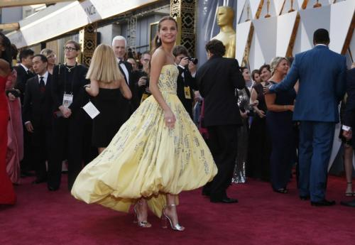 "Alicia Vikander, nominated for Best Supporting Actress in ""Danish Girl,"" wears a yellow Louis Vuitton gown. REUTERS/Lucy Nicholson"
