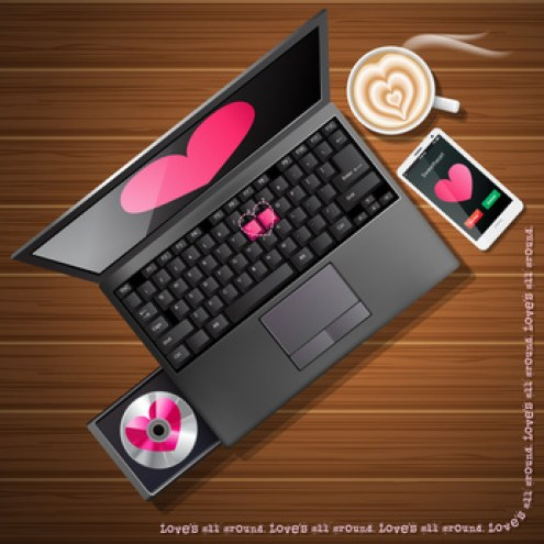 heart shape on laptop screen and mobile phone with latte art on wood background