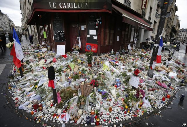 Flowers and candle tributes are placed at the Restaurant Le Carillon in Paris, Nov. 19, 2015, after last Friday's attacks.