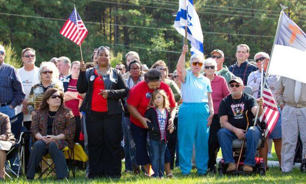 Manifestantes acompanham discursos com bandeiras de EUA e Israel e símbolos cristãos