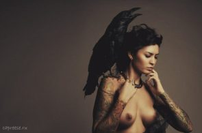 topless woman with a raven on her sholder