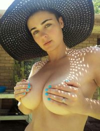 Stefania Ferrario hiding her massive breasts with a gigantic rock