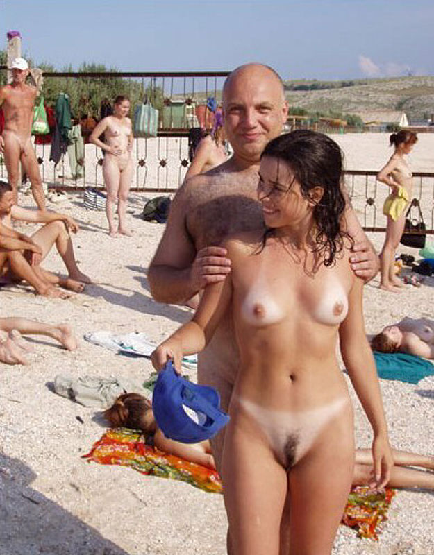 Naked dad and daughter on beach