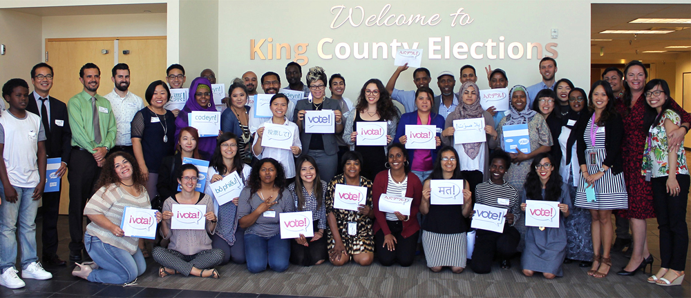 """Community partners hold up """"vote"""" signs in different languages."""