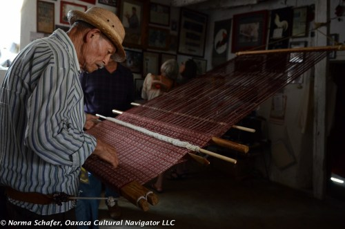 Evaristo bending over the back strap loom