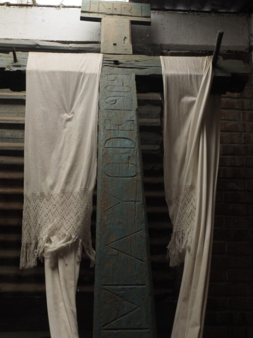 Cross draped with white rebozos in Zarate's workshop corner, a comfort