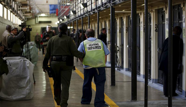 A GUARD ESCORTS A HEARING-IMPAIRED INMATE DOWN A CORRIDOR DURING A MEDIA TOUR OF DEATH ROW AT SAN QUENTIN STATE PRISON IN CALIFORNIA. THIS YEAR SEVERAL STATES ARE LOOKING AT LEGISLATIVE REFORM OF THE DEATH PENALTY AND SOME ARE CONSIDERING REPEALING IT. / PHOTO: (CNS PHOTO/STEPHEN LAM, REUTERS)