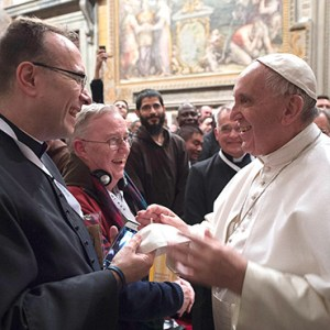 "A CLERGYMAN GIVES POPE FRANCIS A SKULL CAP, OR ZUCCHETTO, DURING A FEB. 9 MEETING WITH ""MISSIONARIES OF MERCY"" AT THE VATICAN. CNS PHOTO/L'OSSERVATORE ROMANO"