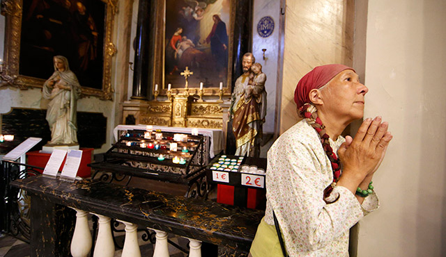 A WOMAN PRAYS AS SHE ATTENDS MASS JULY 15 AT THE NICE CATHEDRAL IN FRANCE TO PAY TRIBUTE TO VICTIMS OF PEOPLE KILLED IN THE BASTILLE DAY ATTACK. POPE FRANCIS PRAYED THAT GOD GIVE COMFORT TO GRIEVING FAMILIES AND FOIL THE PLANS OF THOSE WHO WISH TO HARM OTHERS. PHOTO: CNS PHOTO/ERIC GAILLARD, REUTERS