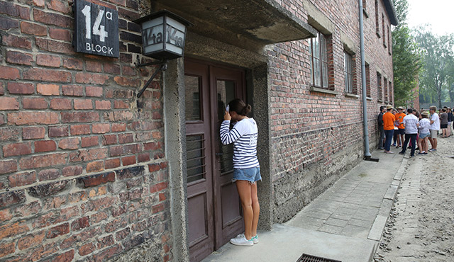A WORLD YOUTH DAY PILGRIM LOOKS INSIDE A BUILDING DURING A JULY 25 VISIT TO THE AUSCHWITZ NAZI CONCENTRATION CAMP IN OSWIECIM, POLAND. / PHOTO: CNS PHOTO/BOB ROLLER