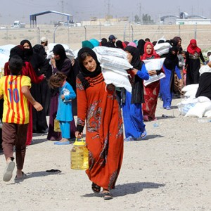 PEOPLE WHO FLED THE ISLAMIC STATE'S STRONGHOLDS OF HAWIJA AND MOSUL RECEIVE AID OCT. 13 AT A CAMP FOR DISPLACED PEOPLE IN DAQUQ, IRAQ. THIS SUMMER, THE U.N. SAID THAT AS THE MOSUL CRISIS EVOLVES, UP TO 13 MILLION PEOPLE THROUGHOUT IRAQ MAY NEED HUMANITARIAN AID BY THE YEAR'S END, FAR LARGER THAN THE SYRIAN CRISIS. CNS PHOTO/AKO RASHEED, REUTERS