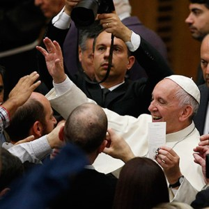 POPE FRANCIS HOLDS A PRAYER CARD AS HE GREETS THE CROWD DURING HIS GENERAL AUDIENCE IN PAUL VI HALL AT THE VATICAN NOV. 23. / PHOTO: CNS/PAUL HARING