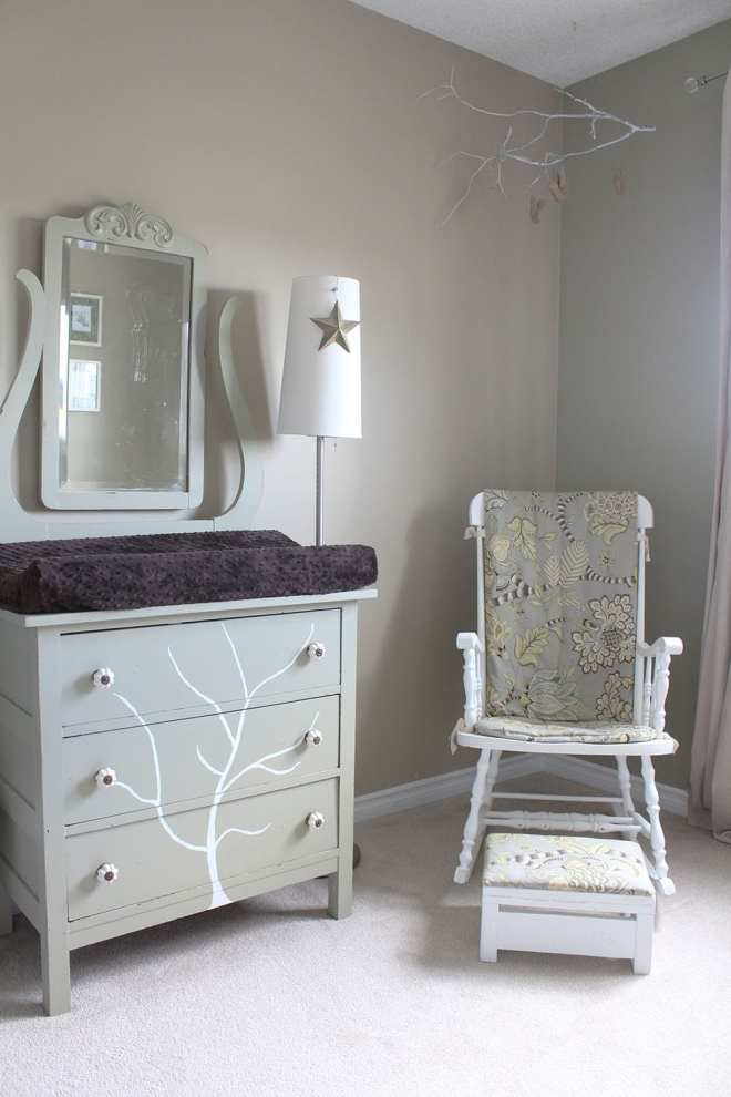 A neutral baby bedroom featuring a handpainted tree dresser and refinished rocking chair.