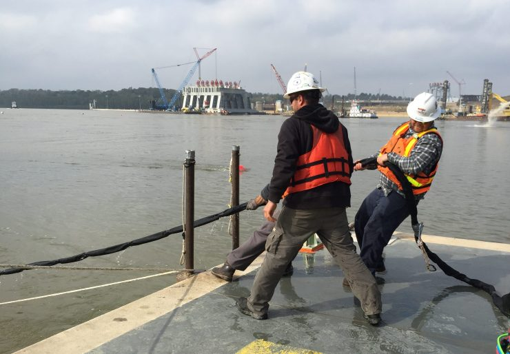 "A support crew pulls a diver to the surface by the ""umbilical"" line at the Olmsted construction site."