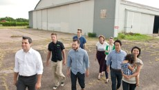 Blair Humphreys, left, leads a group of Design Team members and followers of the Wheeler District Downtown Airpark development effort in front of a hanger onto the surrounding airstrip recently.  (Mark Hancock)