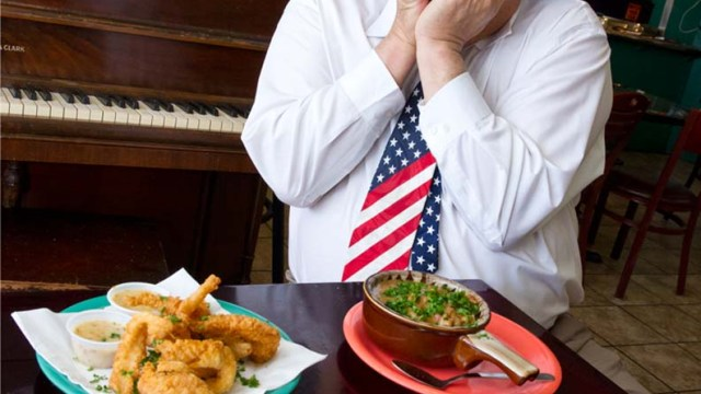 Chicago Dan plays the harmonica at Cajun King regularly. In frony of him sits, fried catfish, etoufe, spicy chicken pasta, and bread pudding. (Shannon Cornman)
