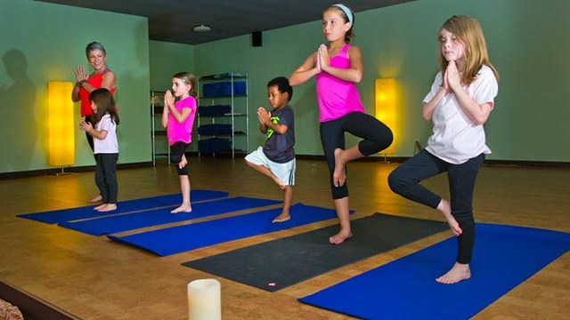 Denise Springer teaches a children's yoga class at You Power Yoga in Edmond.(Shannon Cornman)