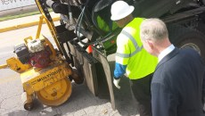 Mayor Mick Cornett watches as a city workers repairs a pothole that was reported using the city's new mobile app. (Ben Felder)