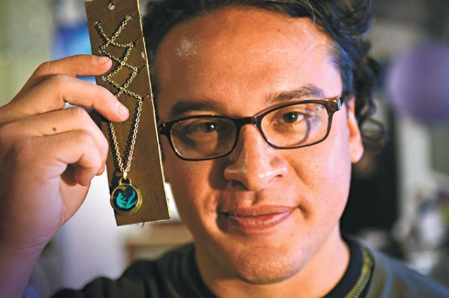 Anthony Pego, artist and proprietor of Boo Science, holds his handmade jewelry. (Mark Hancock)