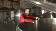Jonathan Stapleton part owner of 405 Brewing Company in Norman, next to on of the large stainless steel brewing vesels.  mh