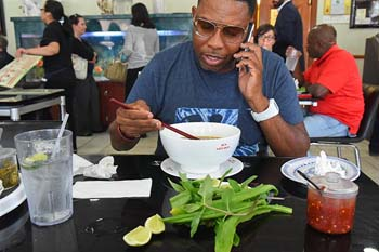 Malik Shakur enjoys his lunch at Pho Lein Hoa, while on the phone.  mh