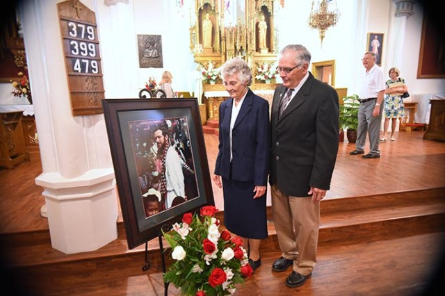 Sister Marita Rother and Tom Rother, siblings of Father Staley Rother, with their deceased brother's portrait. (Mark Hancock)