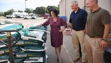 Left to right, Julie Bank, animal welfare superintendent with the Oklahoma City Animal Shelter, receives donation of dog and cat food from Shawnee Milling Company's Brent Thompson, feed sales director, and Joe Ford, vice president of operations, 9-24-15.  (Mark Hancock