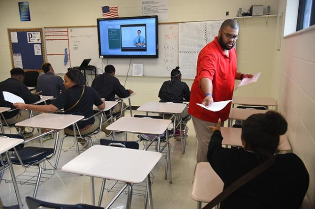 Coach and math teacher Darwin Franklin hands a test to his Algebra I students at Millwood High School.  (Mark Hancock)