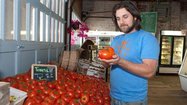 Matt Burch examines a tomato at the Urban Agrarian, in OKC's Farmers Market,  5-3-13  (Mark Hancock)
