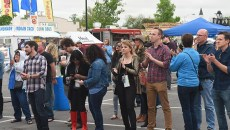 People visiting vendors at a street carnival applaud performers on the Pabst Blue Ribbon Beer Stage nearby. 4-24-2015, during the 2015 Norman Music Festival.  (Mark Hancock)