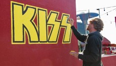 Local artist Rick Sinnett puts finishing touches to some yellow fill in the KISS logo, one of many rock & roll iconic band photos and logos decorating the outside of Rock & Brews restaurant, 2737 W. Memorial Road, 10-27-15.  (Mark Hancock)