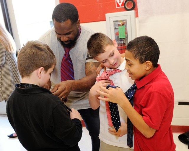 Waylon Kiesewetter and Joshua Shinault show off their ties while Joel Tudman shows Dayton Mitchell how to tie one during a recent Tie Day event at Edgemere Elementary School. (Garett Fisbeck)