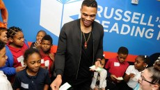 Russell Westbrook presents reading certificates to students during a book fair and opening of Russell's Reading Room at Edwards Elementary School in Oklahoma City, Tuesday, Jan. 5, 2016.  (Garett Fisbeck)