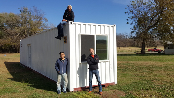 <em>Clockwise from lower left</em> Ben Loh, Swapneel Deshpande and Lee Easton with their ModernBlox container home prototype (ModernBlox / Provided)
