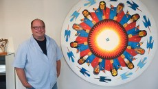 "Eric Oesch, deputy director of Red Earth, with Native American artwork by Commanche artist, Rance Hood called ""Peyote Men"", inside their facility located in the Santa Fe Plaza in Downtown OKC, 10-2-2015.  (Mark Hancock)"