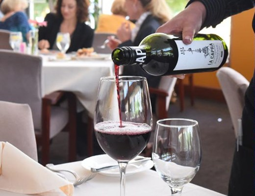 Waitress Elizabeth Wilson pours LA Capra Pinotage wine at the Museum Cafe recently.  mh
