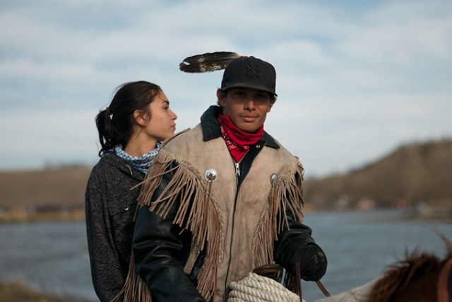 A young man and woman ride horseback at North Dakota's Standing Rock Indian Reservation. (Wade Dunstan / for Oklahoma Gazette)