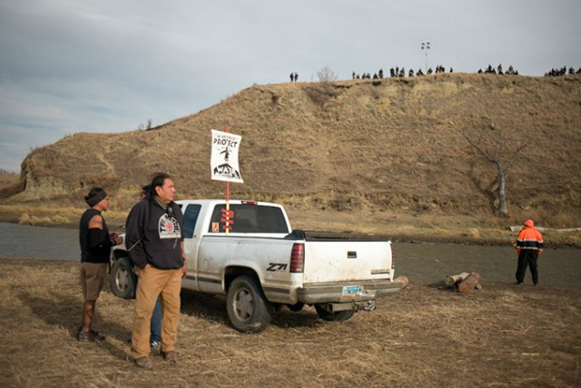 Water protectors attempting to defend Standing Rock Sioux Tribe natural resources and sacred land stand near a river as armed police line up along a hilltop near development of the Dakota Access Pipeline development. (Wade Dunstan / for Oklahoma Gazette)