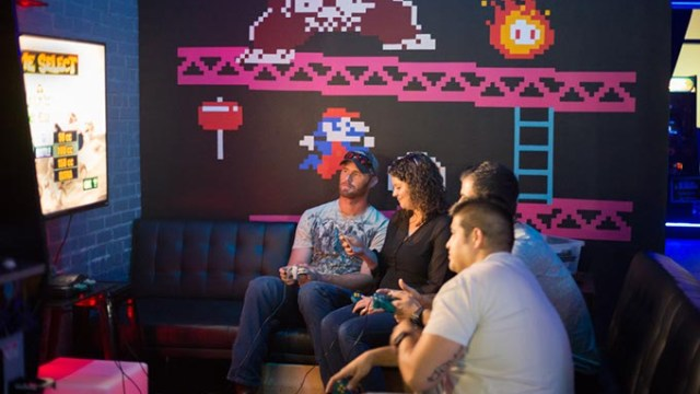 A group plays retro video games at the Flash Back Retro Pub 90's Night on Saturday, July 30, 2016 in Oklahoma City.  (Emmy Verdin)