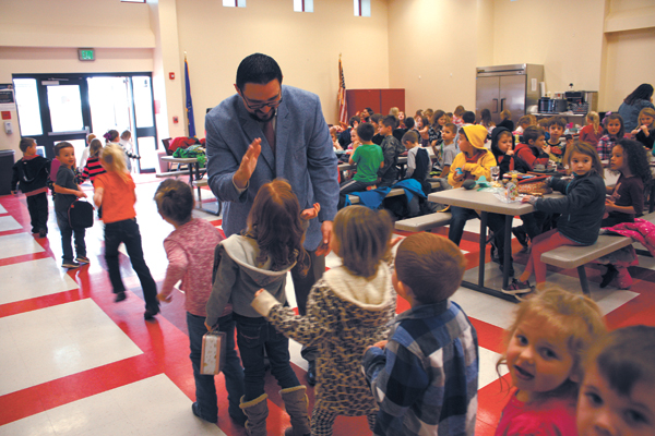 Brandon Voss high-fives students as they pass through the Robin Hill cafeteria. (Laura Eastes)