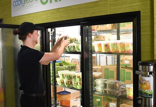 A worker re-stocks the selection of the Grab and Go items at the re-opened downtown CoolGreens.  mh