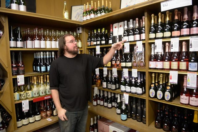 Freeman's Liquor Mart sales consultant Brett Fieldcamp explains the variety of international sparkling wines good for drinking or using in cocktails. (Garett Fisbeck)
