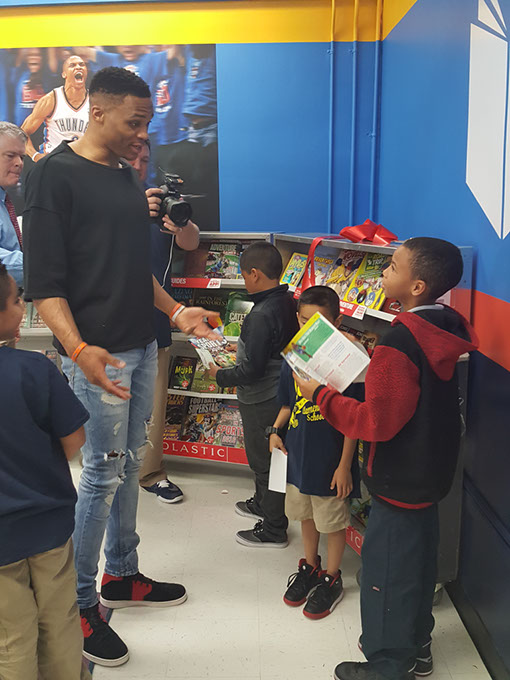 Russell Westbrook helped students choose books at the opening of his Russell's Reading Room at Adams Elementary on March 21. (Michael Kinney / for <em>Gazette</em>)