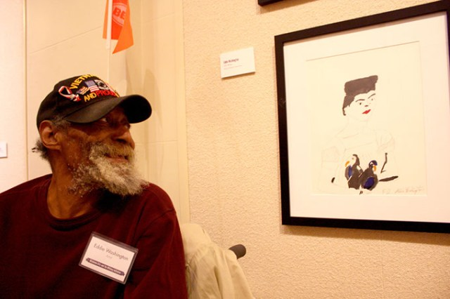 U.S. Army veteran Eddie Washington views his work, which is on display in the Governor's Gallery at the Oklahoma Capitol. Washington was one of many veterans who participated in an Oklahoma Arts and the Military Initiative. (Laura Eastes)