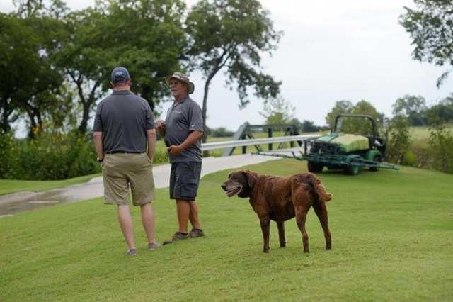 Chris Chesser, golf course director, and Derron Day, course superinendent, talk as Scout looks on at Firelake Golf Course in Shawnee, Monday, July 31, 2017.  (Garett Fisbeck)