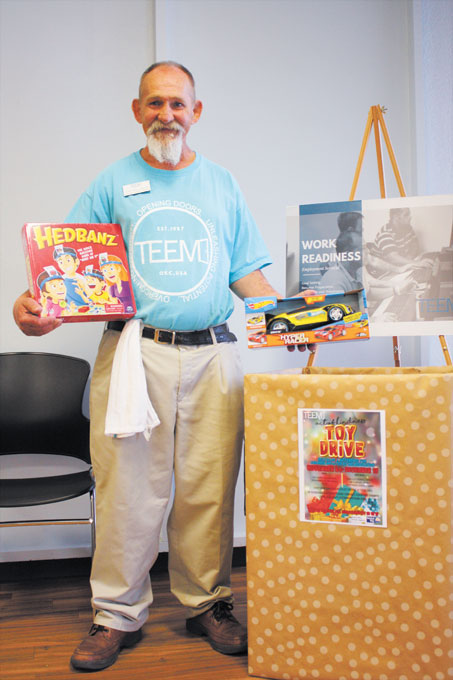 Tony Williamson, a former TEEM participant and now employee, holds two holiday gifts donated to be distributed to Oklahoma children who have a parent in prison this holiday season. (Laura Eastes)